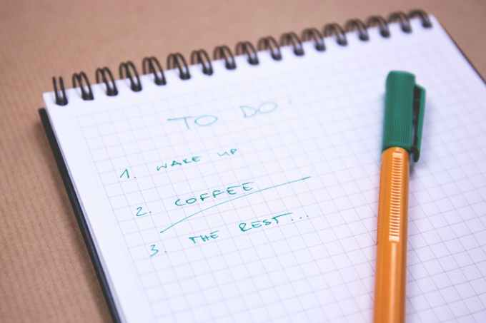 Pen and notepad with a to-do list written on it. On the to-do list reads: 1. Wake up 2. Coffee 3. The Rest...