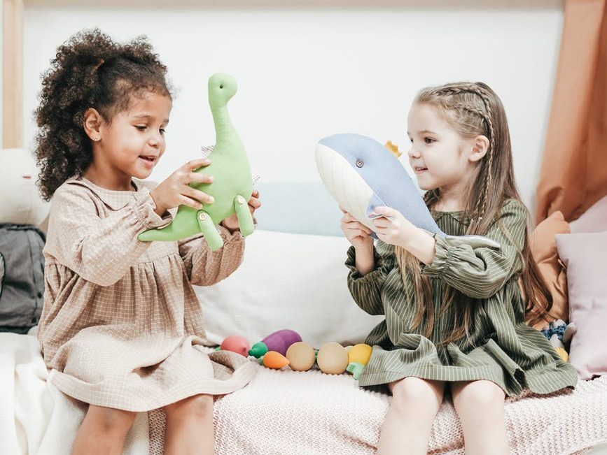 two toddler girls playing, one has a stuffed whale and the other has a stuffed dinosaur